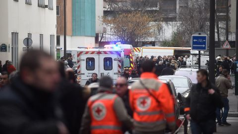 Ambulances and police officers gather in front of the building.