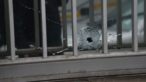 A bullet hole is seen in a window of the magazine's building.