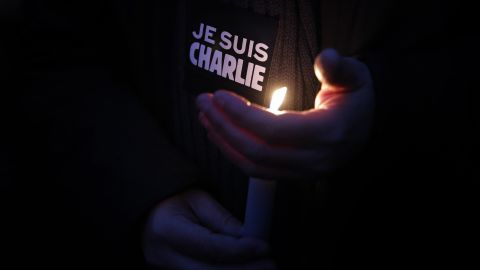 """A man holds a candle and a sticker that translates to """"I am Charlie"""" during a vigil in Paris on January 7."""