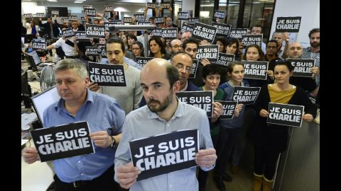 """Journalists with Agence France-Presse hold signs reading """"I am Charlie"""" as they observe a minute of silence on January 7."""
