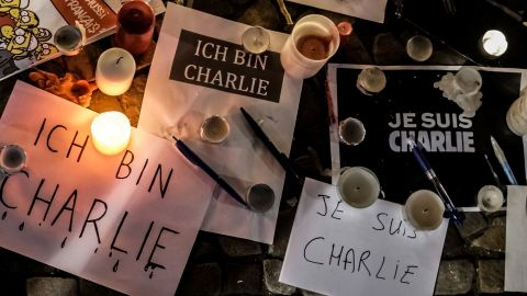 """Papers with """"I am Charlie"""" written in various languages are left near candles at a vigil in front of the French Embassy in Berlin."""