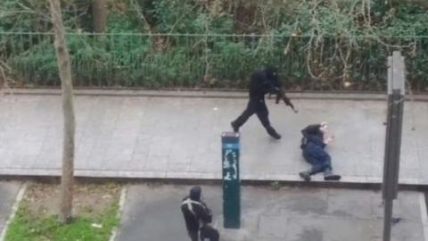 Masked gunmen run toward a victim.
