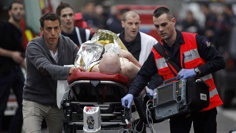 An injured man is taken away for medical care.