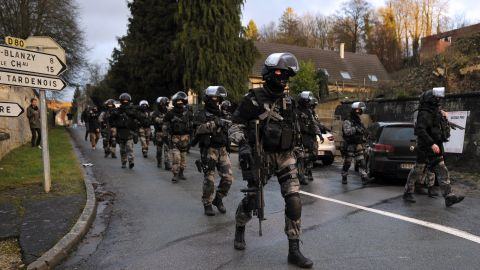 Police walk down a street in Corcy, France, on January 8.
