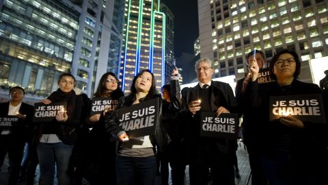 """Journalists and other people in Hong Kong hold up pens and hold signs that say """"Je suis Charlie"""" (I am Charlie) during a vigil on January 9."""