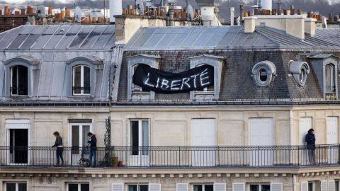 """A banner attached to a house overlooking the Place de la Republique reads """"Freedom"""" as thousands of people gather below."""