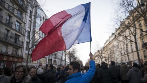 A young man waves a French national flag in the streets of Paris.