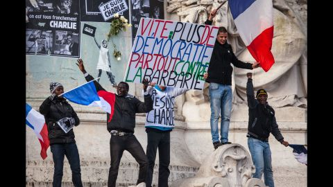 """Demonstrators hold a sign that translates as """"Urgent: More democracy everywhere against barbarism."""""""
