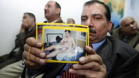 An Iraqi victim of a shooting incident holds up a picture of himself, during a meeting with US Federal Prosecutors to discuss the case against the security firm Blackwater at the central police station close to Nussur Square in central Baghdad on December 13, 2008.