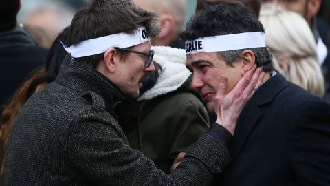 """Patrick Pelloux (right), a journalist at Charlie Hebdo, is embraced by Renald """"Luz"""" Lucier (left), a cartoonist at the magazine."""
