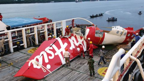 Crew members of Crest Onyx ship prepare to unload parts of AirAsia Flight 8501 from a ship at Kumai port in Pangkalan Bun,Sunday, Jan.11, 2015. A day after the tail of the crashed AirAsia plane was fished out of the Java Sea, the search for the missing black boxes intensified Sunday with more pings heard. (AP Photo/Achmad Ibrahim)