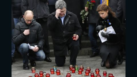 Ukrainian President Petro Poroshenko, center, his wife Maria,right, and Ukrainian Prime Minister Arseniy Yatsenyuk, pay their respects during a rally on Sunday, January 18 at Independence Square in Kiev, Ukraine.  The rally was to show solidarity with the victims of a rocket  that claimed 13 lives on a highway near the town of Volnovakha.