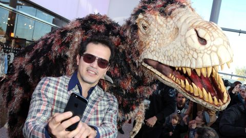 """Actor John Leguizamo shoots a selfie at the """"Walking with Dinosaurs"""" press event at the Los Angeles Natural History Museum."""