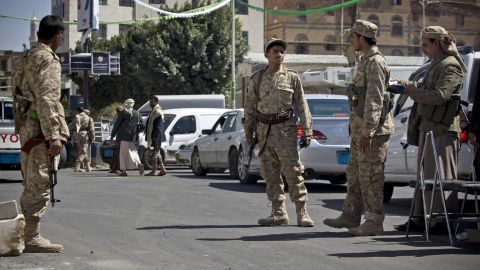 Houthi men wearing army uniforms stand guard on a street leading to the presidential palace in Sanaa on Wednesday, January 21.