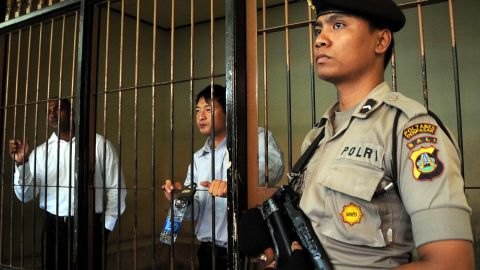 n Indonesian policeman stands guard next to a detention room where Australians Myuran Sukumaran (L) and Andrew Chan (C), members of the so called Bali Nine gang, wait for their trial in Denpasar on the island of Bali on October 8, 2010. An Indonesian prison chief testified on October 8, that two Australian drug smugglers on death row have given great contribution in teaching fellow inmates and should not be executed. Andrew Chan and Myuran Sukumaran, members of the so-called Bali Nine gang, are seeking 20 years to life in prison for a 2005 attempt to smuggle 8.3 kilograms (18 pounds five ounces) of heroin into Australia from Bali island. AFP PHOTO / SONNY TUMBELAKA (Photo credit should read SONNY TUMBELAKA/AFP/Getty Images)