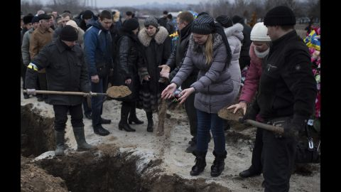 People in Mariupol, Ukraine, pour soil into the grave of a recent shelling victim on Monday, January 26.