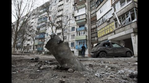 A piece of an exploded missile sits lodged in the ground outside an apartment building in the Vostochniy district of Mariupol on Sunday, January 25.