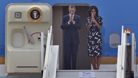U.S. President Barack Obama and first lady Michelle Obama fold their hands together in a traditional Indian greeting gesture as they prepare to board Air Force One in New Delhi, India, January 27, 2015.