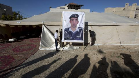 A banner with a picture of al-Kasasbeh is raised by workers near a tent in Amman on Friday, January 30.