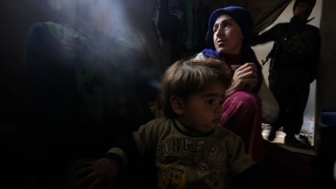 """Zehra, a 25-year-old Kurdish woman who lost her 8-month-old daughter due to a lung infection at a refugee camp, sits with her other daughter inside their home in Kobani, Syria, on Thursday, January 29. Her husband, a fighter from the People's Protection Units, or YPG, stands in the background. After four months of intense fighting, Kurdish Peshmerga forces <a href=""""http://www.cnn.com/2015/02/04/middleeast/kobani-syria-destruction/index.html"""" target=""""_blank"""">have liberated Kobani</a> from the grip of the ISIS militant group. Click through to see more photos of Kobani taken recently by Ricardo Garcia Vilanova."""