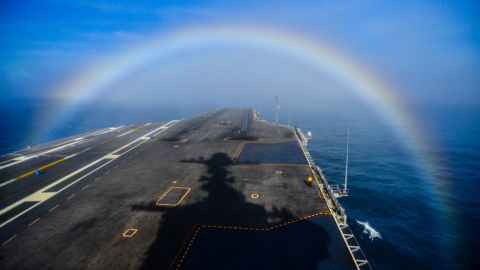 A rainbow forms over the bow of the Nimitz-class aircraft carrier USS John C. Stennis as the ship steams in the Pacific Ocean on February 3, 2015.