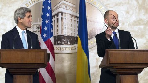 Ukraine Prime Minister Arseniy Yatsenyuk, in Kiev with U.S. Secretary of State John Kerry, offers his glasses to Russian President Vladimir Putin.