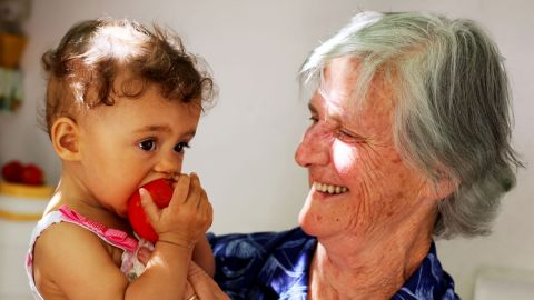Antiiopi Koufadakis, an 80-year-old cancer survivor, feeds a homegrown tomato to her granddaughter. Her father lived to 98.