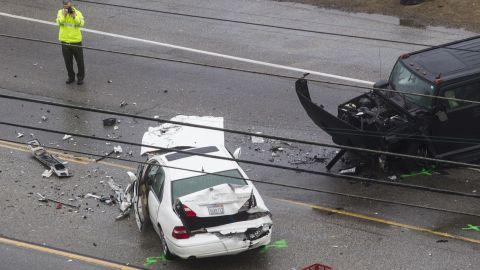 A Los Angeles County Sheriff's deputy photographs the scene. One of the drivers involved in the wreck was killed on Pacific Coast Highway near Corral Canyon Road, a news release stated.