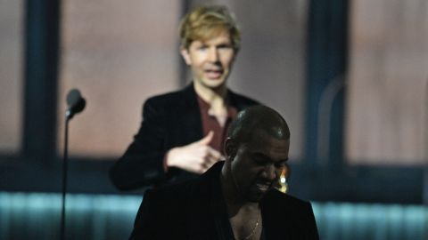 Beck, left, reacts as Kanye West leaves the stage after Beck won album of the year at the Grammys.