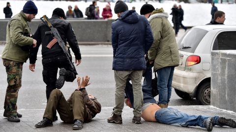 Ukrainian volunteer fighters and policemen arrest two men in Kiev, Ukraine, on February 9. The men allegedly arrived from Donetsk and were suspected of participating in pro-Russian rebel activities and organizing terrorist attacks in the Ukrainian capital.