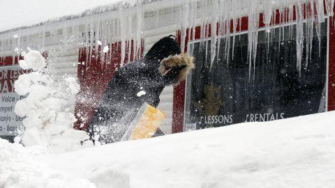 Corbit Larson clears snow in front of his Centre Music House store in Framingham, Massachusetts, on February 9.