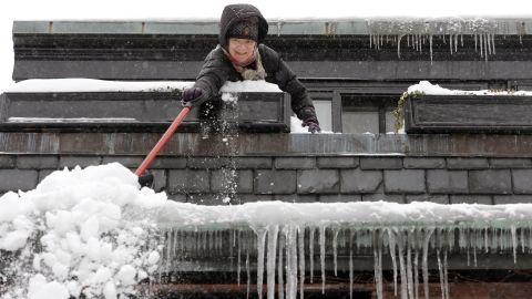Susan Hartnett shovels snow from the roof of her Beacon Hill home in Boston on February 9.