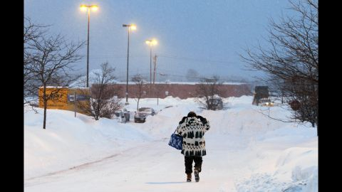 A woman walks down a snow-covered road in Marlborough early on February 9.
