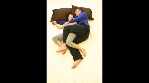 """A hybrid of the classic """"spooning"""" method, this position allows for room to touch and talk. To recreate the position, start with a basic spoon and then bend legs as though riding a bike, intertwining arms and legs."""