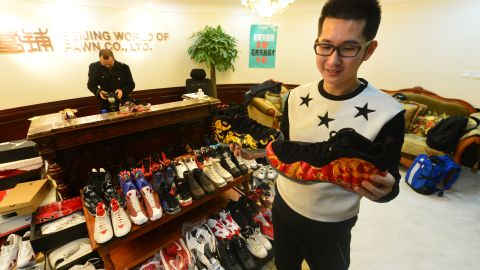 A Chinese man, who gave the English name Mick,  looks at the 283 pairs of shoes he pawned off to make down-payment on an apartment.
