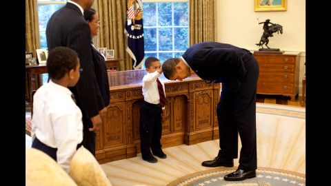 """Obama bends over so the son of a White House staff member can pat his head during a visit to the Oval Office in May 2009. The boy <a href=""""http://newsroom.blogs.cnn.com/2009/05/15/hair-apparent/"""" target=""""_blank"""">wanted to know </a>if Obama's hair felt like his."""