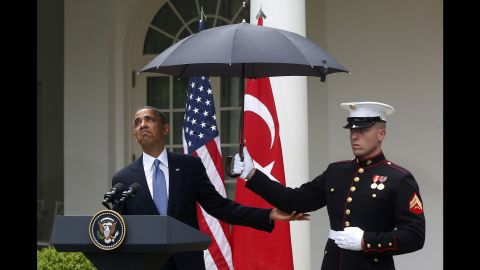 Obama adjusts an umbrella held by a Marine during a White House news conference with Turkish Prime Minister Recep Tayyip Erdogan in May 2013.