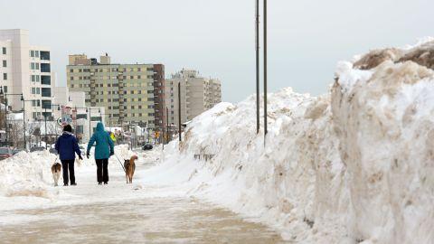 Women walk their dogs along Revere Beach on February 14 in Revere, Massachusetts.