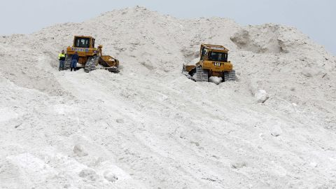 """A pair of bulldozers rest on a giant pile at a """"snow farm"""" in Boston on February 14."""