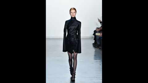 A model walks in a tailored turtleneck look with extended cuffs for Misha Nonoo.