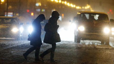 Pedestrians cross the street as snow falls in Boston on Saturday, February 14.