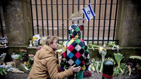 People stand by a makeshift memorial outside a synagogue where an attack took place in Copenhagen, Sunday, February 15. Danish police shot and killed a man early Sunday suspected of carrying out shooting attacks at a free speech event and then at a Copenhagen synagogue.