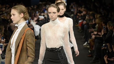 A model walks the runway in a high, lace neckline for Altuzarra.