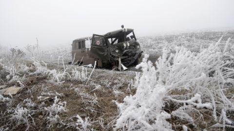 An army ambulance damaged in recent shelling lies by a road near Svitlodarsk, Ukraine, on Sunday, February 15.