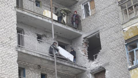 People carry a refrigerator through a balcony at an apartment building that was damaged in recent shelling in Svitlodarsk on February 15.