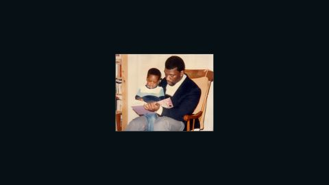 Benjamin Watson sits on his dad's lap while reading a book
