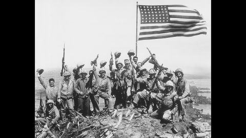"""This image is referred to as Rosenthal's """"gung ho"""" photo, in which Marines posed with the second flag while raising their rifles and helmets in the air. When Rosenthal was asked later if the image was posed, he said it was. That created confusion over whether his photo of the actual flag-raising was posed. For years many people thought it was, but it really was not."""
