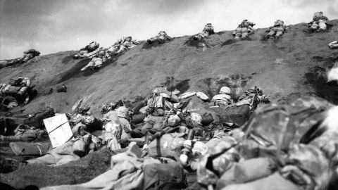 In the face of enemy fire, Marines inch their way over the slope on Red Beach No. 1. In the foreground, other Marines huddle in shell holes as they wait for orders to move forward.