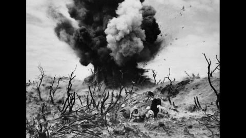 US Marines take cover as a cave is blown up on Iwo Jima.