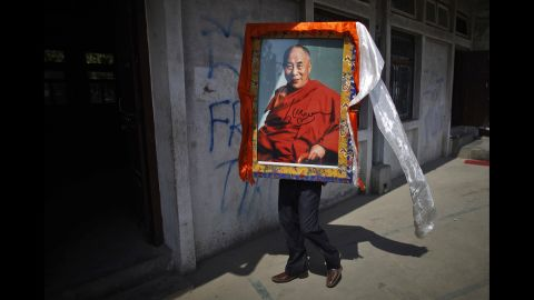 A Tibetan man in Katmandu, Nepal, carries a portrait of the Dalai Lama on April 25, 2012, during an event marking the 23rd birthday of Panchen Lama Gendun Choekyi Nyima, the second-highest Tibetan religious leader.